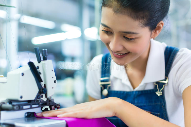 Indonesian seamstress in a textile factory stock photography