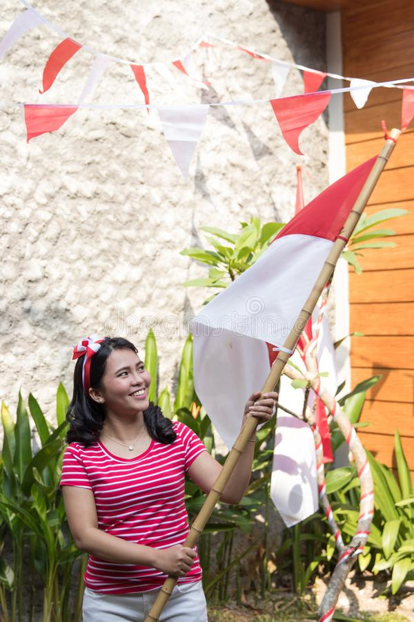 Indonesian woman with indonesia flag during independence. Day celebration at home stock photo