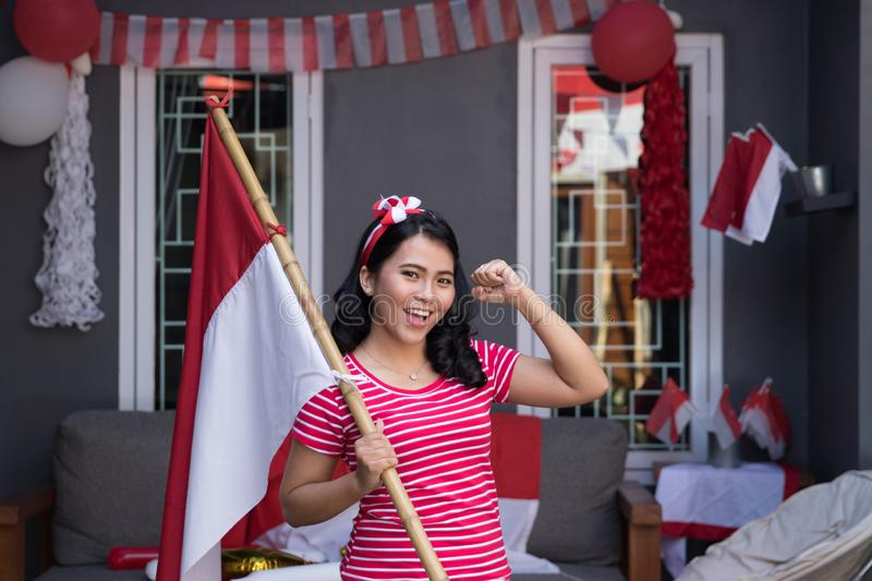 Indonesian woman with indonesia flag during independence. Day celebration at home stock images