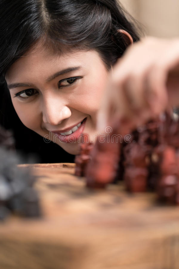 Indonesian woman playing chess setting figure stock photography