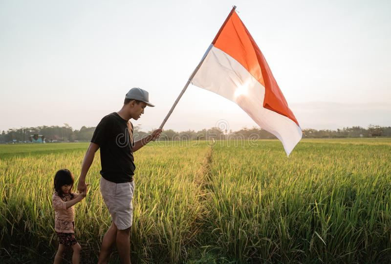 Indonesian young father and hers daughter holding bamboo stick with big flag. Of Indonesian in the rice field stock image