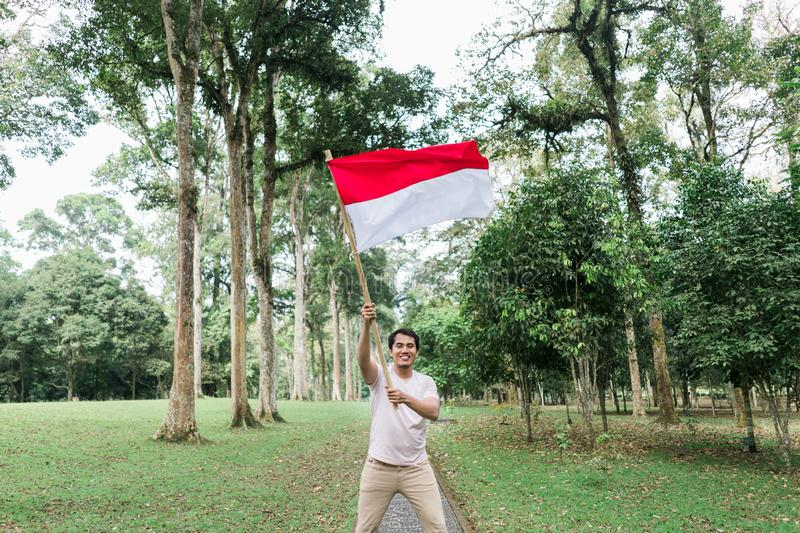 Indonesian young man holding bamboo stick with big flag. Of Indonesian in the park stock photography