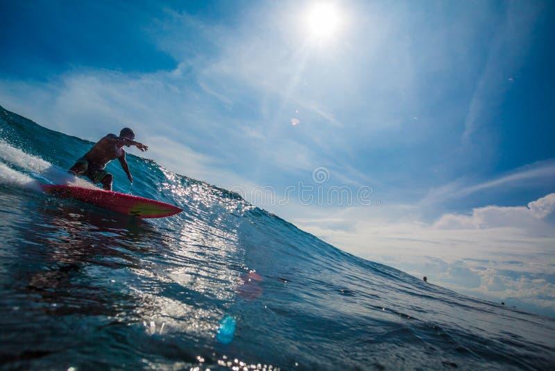 Indonesien Bali, Juli 13 2016: En manlig surfare som rider stor blå oce arkivbild