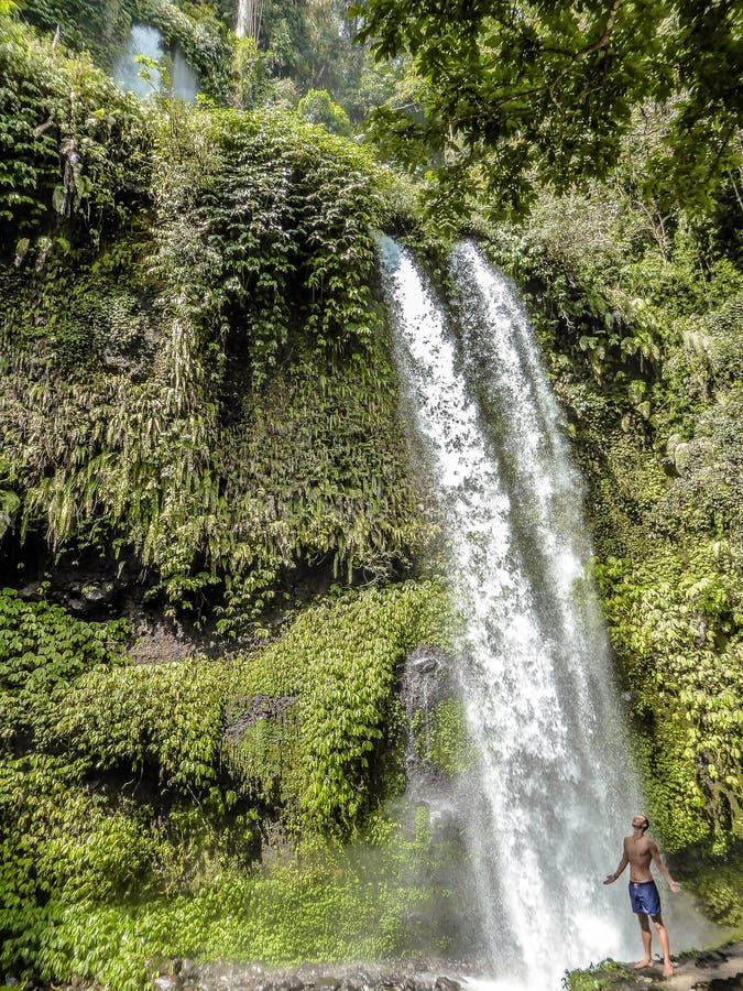 Indonesien - der Mann und der Wasserfall stockfotos