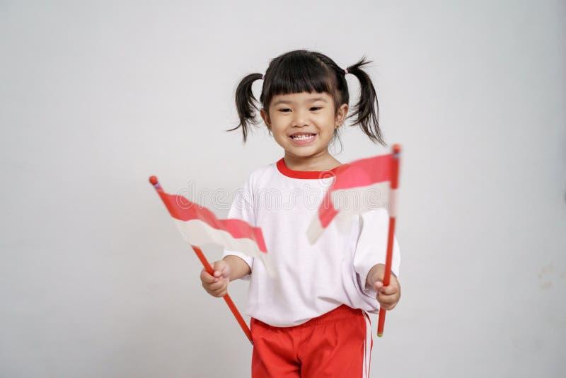 Indonesisch jong geitje die aan camera met vlag glimlachen stock foto's