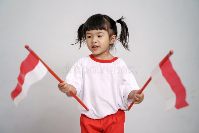 Indonesisch jong geitje die aan camera met vlag glimlachen royalty-vrije stock fotografie