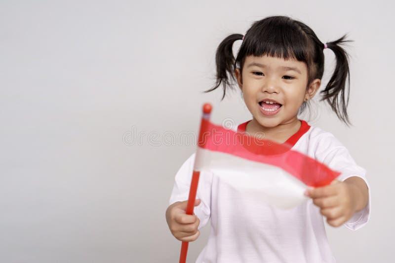 Indonesisch jong geitje die aan camera met vlag glimlachen royalty-vrije stock afbeelding