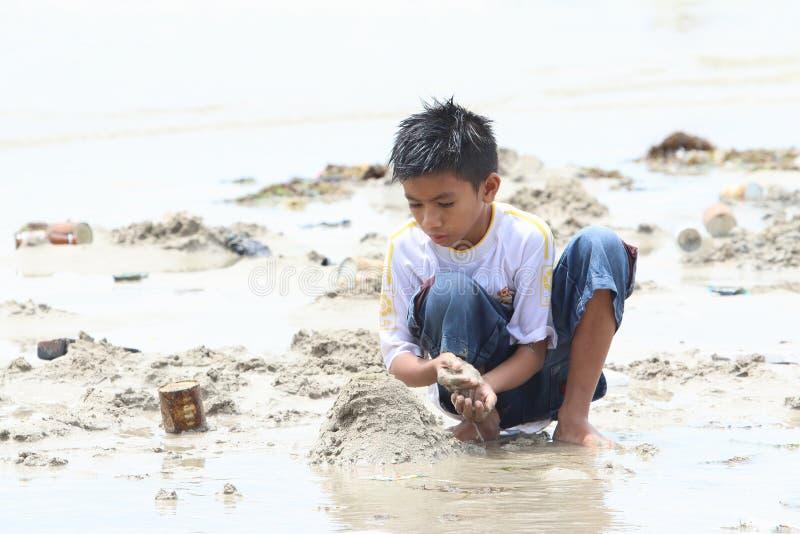 Indonesisch jong geitje - jongen het spelen op strand stock fotografie