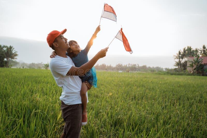 Indonesisch jong geitje met vaderspel met nationale vlag royalty-vrije stock afbeelding