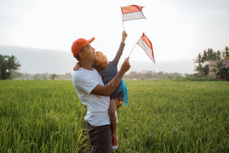 Indonesisch jong geitje met vaderspel met nationale vlag stock foto's