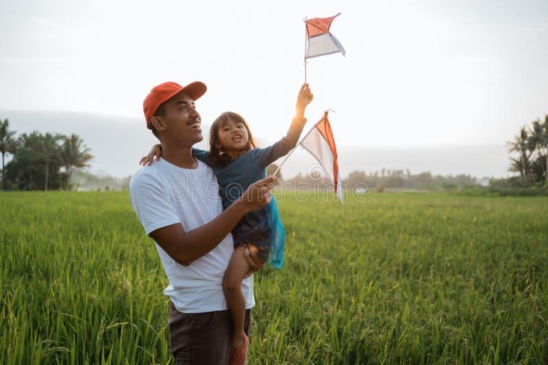 Indonesisch jong geitje met vaderspel met nationale vlag stock afbeelding