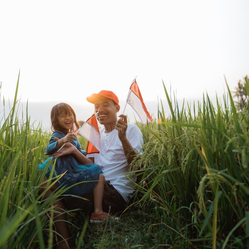 Indonesisch jong geitje met vaderspel met nationale vlag royalty-vrije stock fotografie