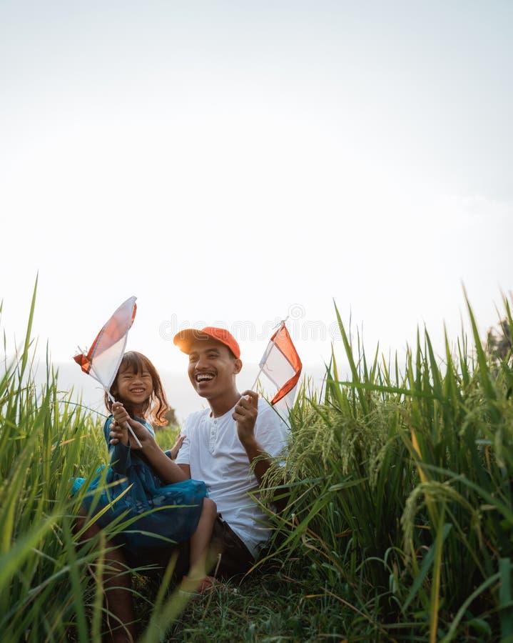 Indonesisch jong geitje met vaderspel met nationale vlag stock fotografie