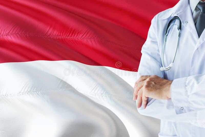 Indonesische Arts die zich met stethoscoop op de vlagachtergrond van Indonesië bevinden Het nationale concept van het gezondheids stock foto's