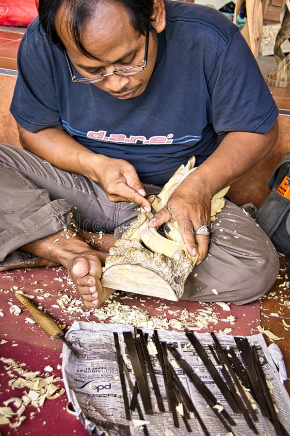 Indonesische het kabinetsarbeider die van de mensentimmerman met een beitel in zijn workshop, die aan de vloer werken zitten Het  royalty-vrije stock fotografie