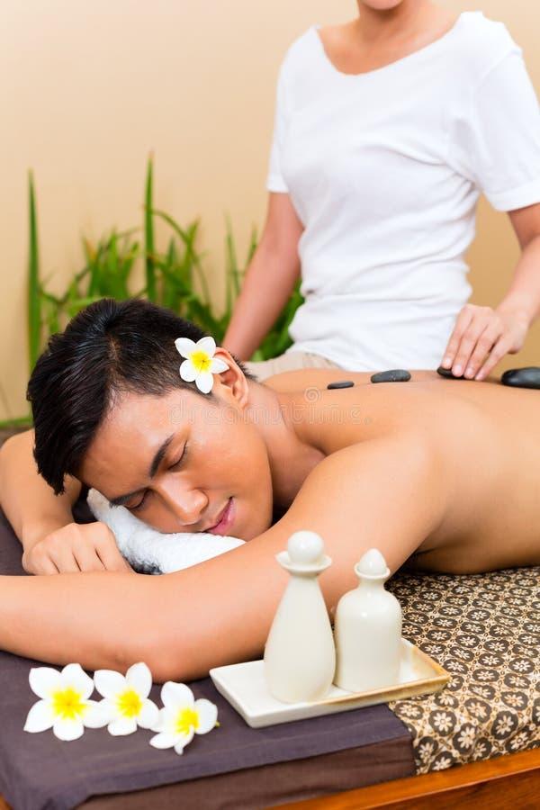 Indonesische mens bij de hete massage van steenwellness stock foto's