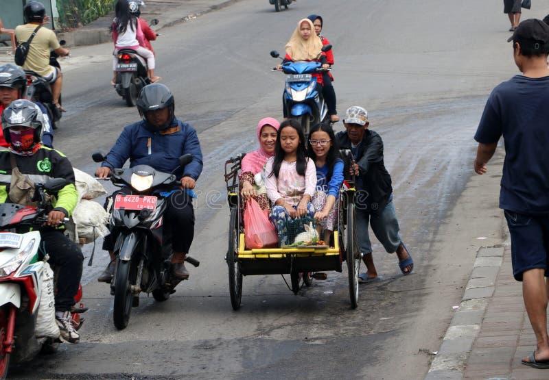Indonesische mens die zijn fietstaxi met drie wielen met passagier drie naar omhoog duwen aan steil van de brug op de weg in Djak royalty-vrije stock fotografie