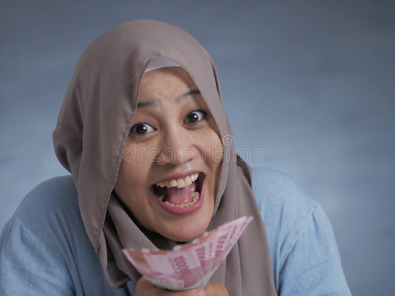 Indonesische Muslimfrau Holding Rupiah Money stockfotos