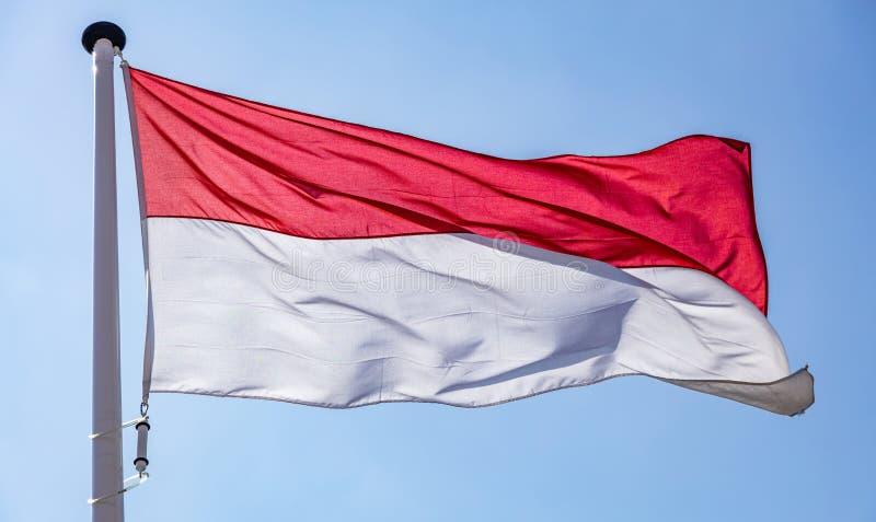 Indonesische vlag die tegen duidelijke blauwe hemel golven stock foto