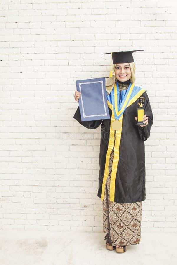 Indonesische vrouwelijke gediplomeerde student die graduatietoga dragen whil royalty-vrije stock foto