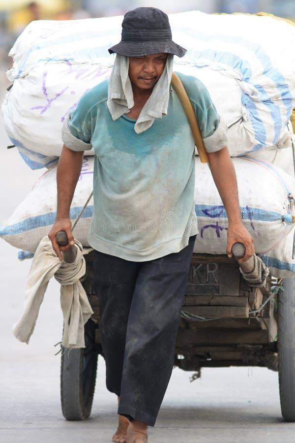 Indonesischer Hafenarbeiter Sunda Kelapa im Kanal, Jakarta lizenzfreie stockfotografie