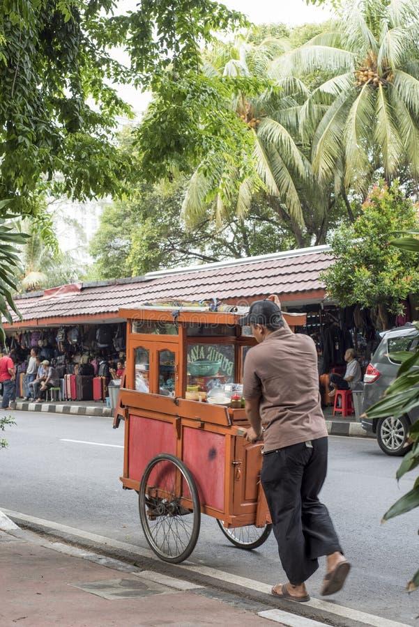 Indonesischer Mann drückt einen Nahrungsmittelwagen an an der Antike und dem Floh Jalan Surabaya stockfotografie