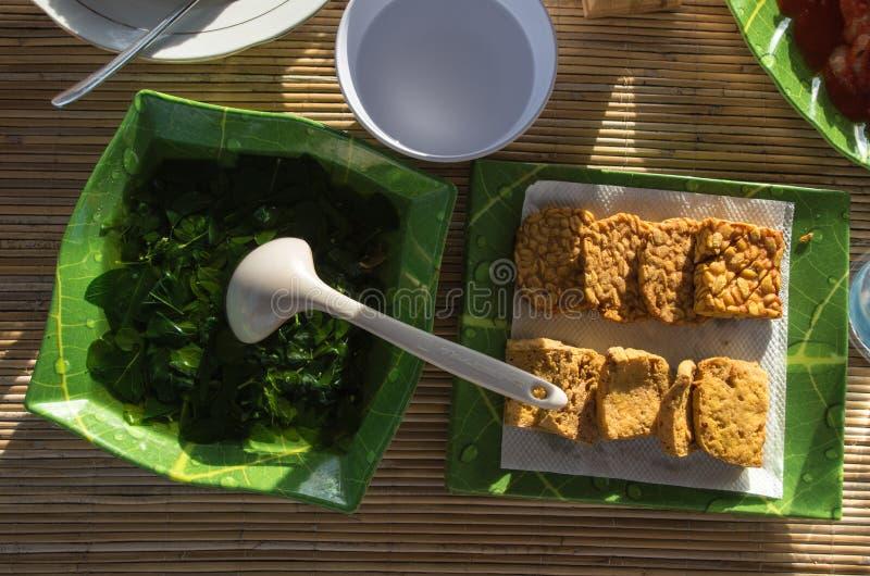 Indonesischer Spinat sowie Tempe- und Tofugoreng brieten Tofu und Tempe stockfotos