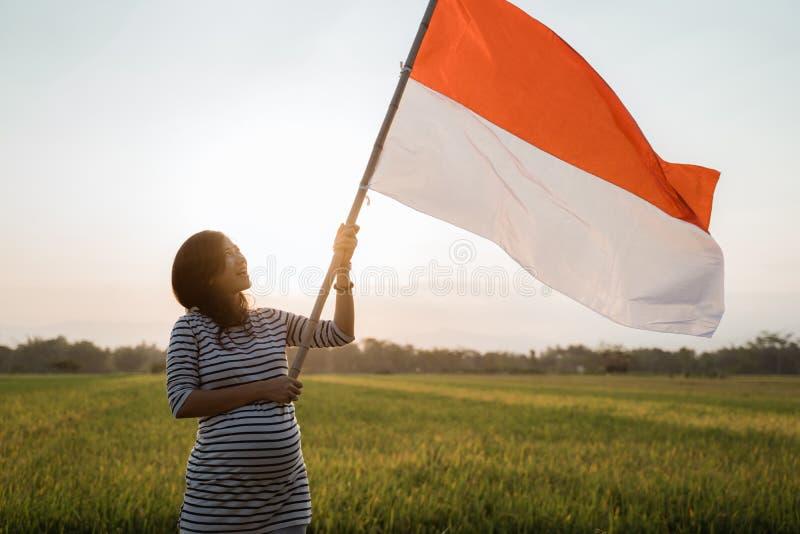 Indonesisk gravid kvinna som rymmer bambupinnen med den stora flaggan royaltyfri foto