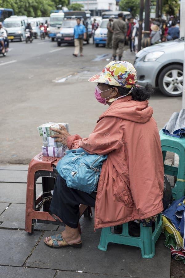 Indonesiska kvinnautbytesvalutor i en gata av Jakarta nära den Kota stationen arkivbild