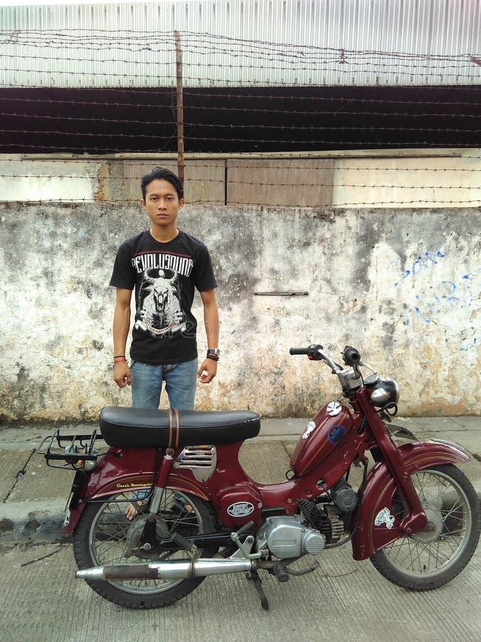 Indonezyjska chłopiec z jego motorowym rowerem obrazy royalty free