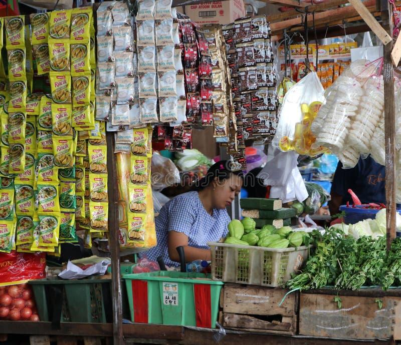Indonezyjski żeński sprzedawcy ulicznego obsiadanie w jej sklepu spożywczego sklepie przy świeżym rynkiem w Dżakarta fotografia royalty free