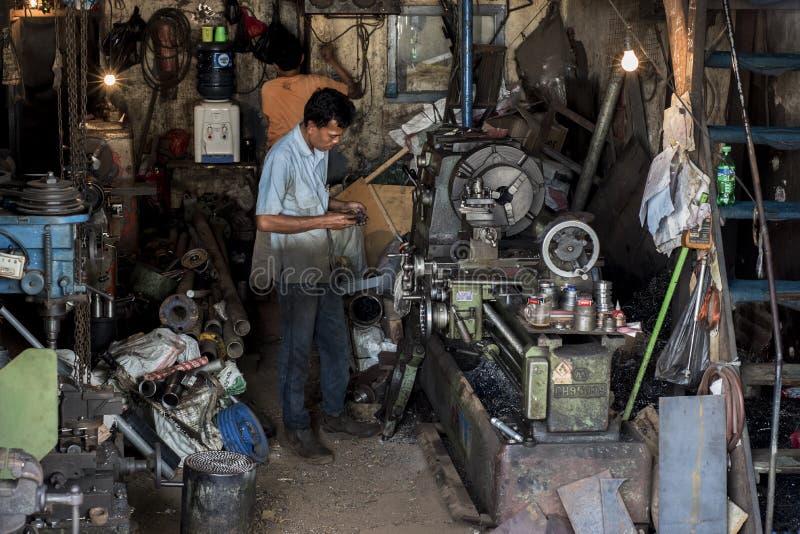 Indonezyjski pracownik działa jego maszynę w starym worshop w Dżakarta, Indonezja obraz stock