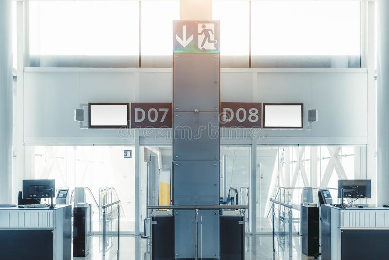 Indoor airport gates. An empty gates of a modern airport terminal with computer monitors on the counter desks, information screens on the top, baggage gauge, and stock photo