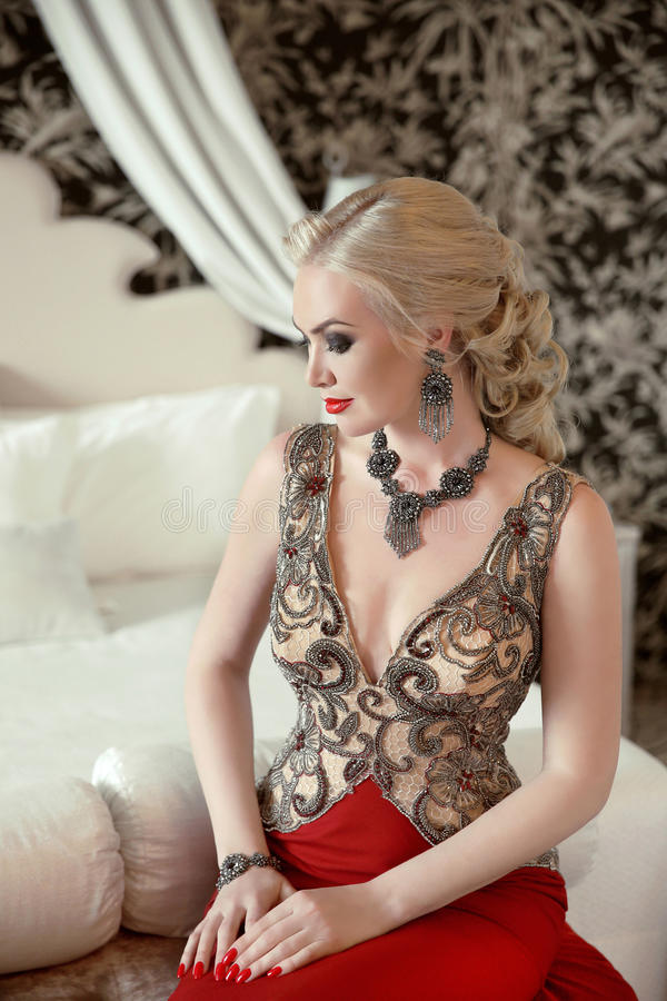 Indoor beauty portrait of blond woman in fashion jewelry and lux stock photo