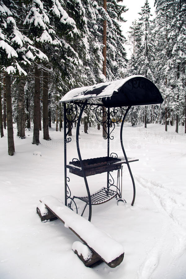 Indoor brazier in winter in the woods. With a wooden bench royalty free stock photo