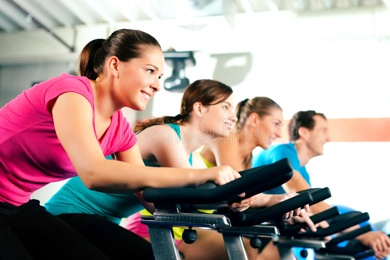 Indoor bycicle cycling in gym royalty free stock photography