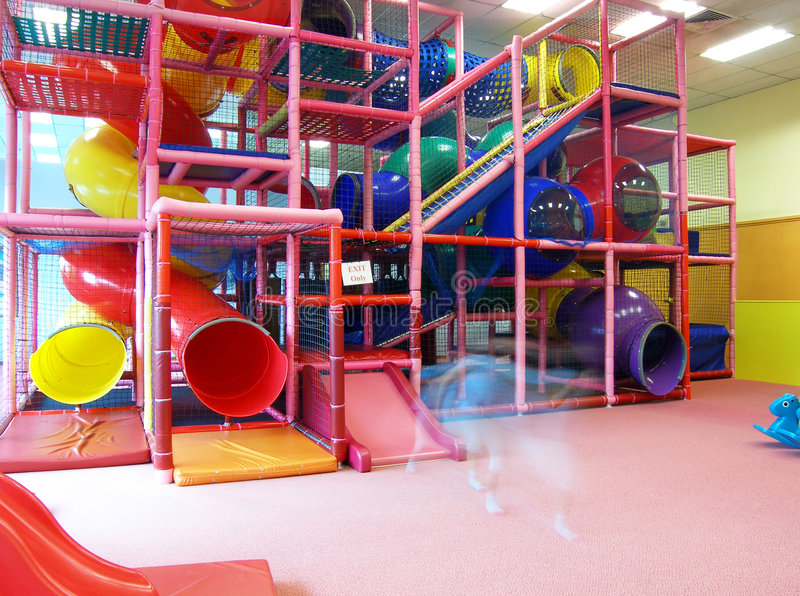 Indoor children playground structure. An image of a huge and fun indoor children composite play equipment, a facility at a country club. With safety nets around royalty free stock images