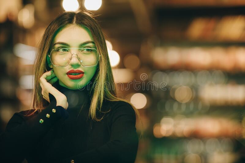 Close up portrait of beautiful fashionable woman posing in loft interior. Model looking through window. Lady wearing royalty free stock photo