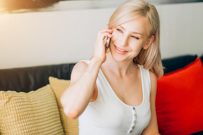Young woman using phone while relaxing on sofa stock images