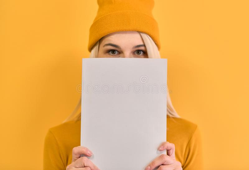 Indoor closeup monochrome portrait of of cheerful woman covers face with white book, has joyful expression, blank copy space for royalty free stock photos