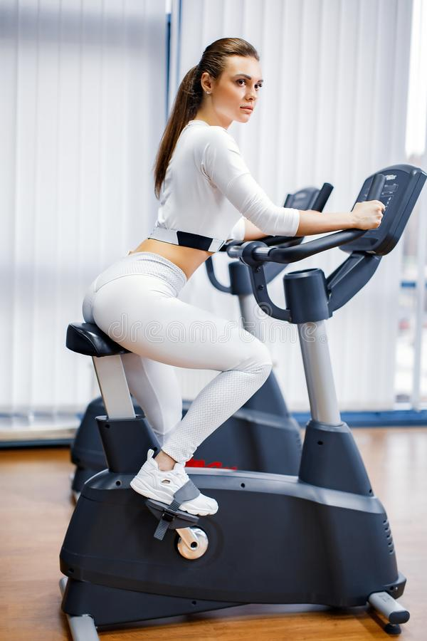 Indoor cycling woman doing cardio workout biking on indoors gym bike. Indoor cycling woman doing HIT cardio workout biking on indoors gym bike. Girl cyclist stock photos
