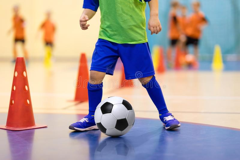 Indoor football futsal training for children. Soccer training dribbling cone drill. Indoor soccer young player with a soccer ball. Football futsal training for stock photography