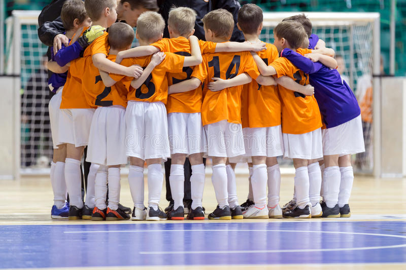 Indoor football soccer match for children. Coach giving young so stock image