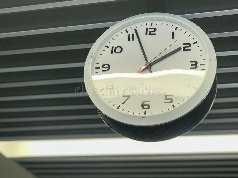 Hanging round clock in the building stock photos