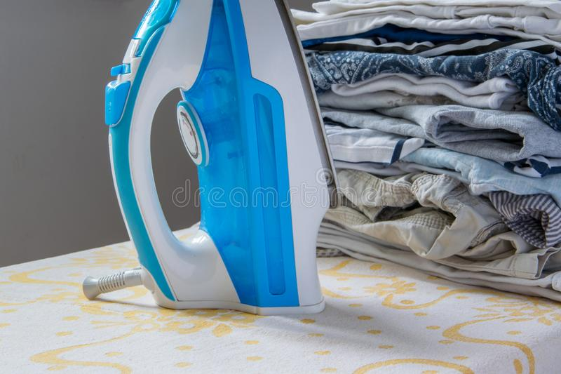 Indoor housework - steam iron and pile of folded clothes. In background stock photos