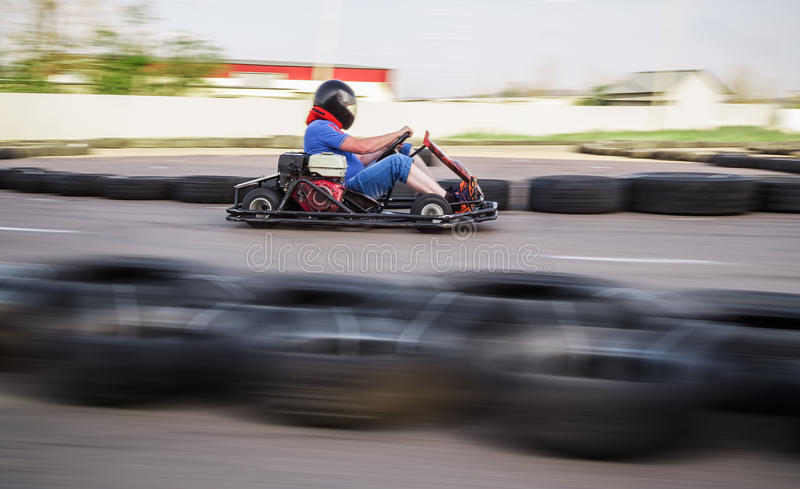 Indoor karting race. Rushing kart and safety barriers stock photo