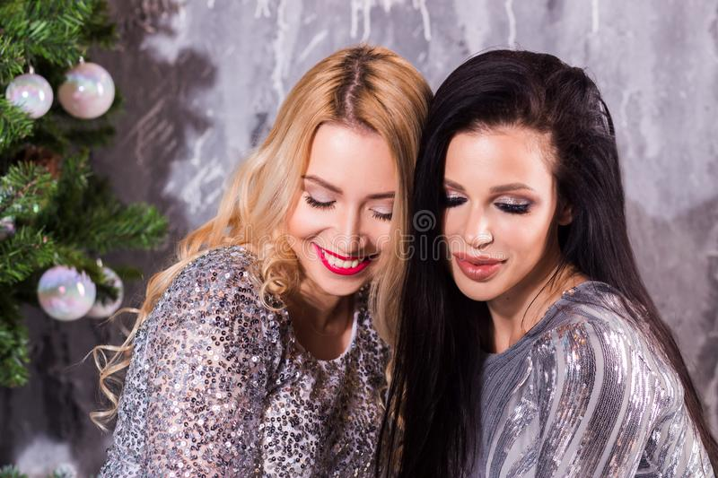 Indoor lifestyle portrait of two friends with eyes closed, elegant women in evening dress Holiday makeup and bright party. Accessories posing on grey wall royalty free stock images