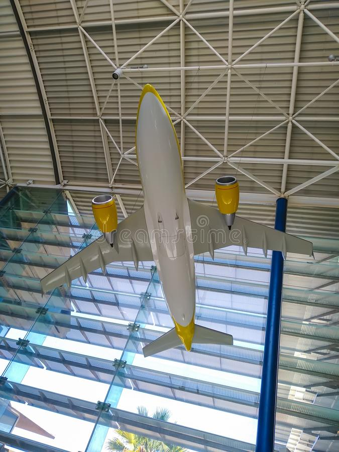 An indoor miniature white and yellow plane hanging from the ceiling of an airport demonstration the aeronautic technology where. The passengers will fly in one stock images