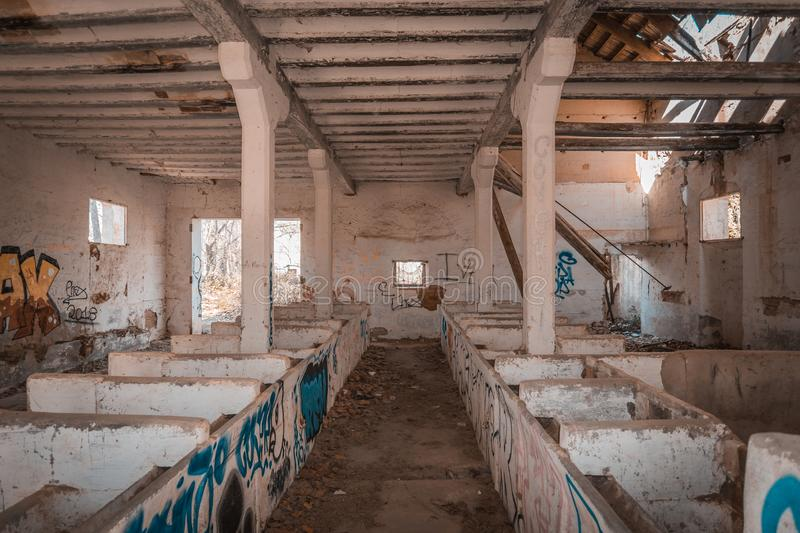 Indoor of an old animal corral. Abandoned and partially sunk, full of graffiti and with cross beams partially fallen royalty free stock images
