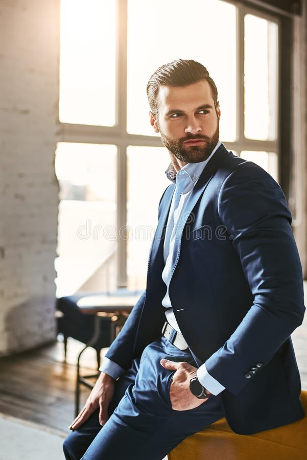 Indoor photo of young european businessman in elegant suit standing at modern office amd looking away stock image